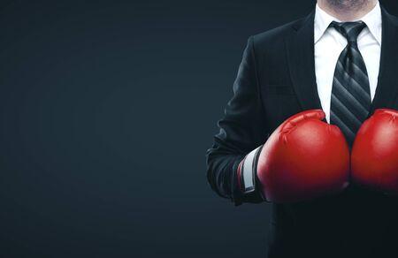 Geschäftsmann in roten Boxhandschuhen auf grauem Hintergrund isoliert. Geschäftsherausforderungskonzept Standard-Bild