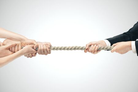 Businessman and various hands during tug war on gray backgrounds. Business competition concept Standard-Bild