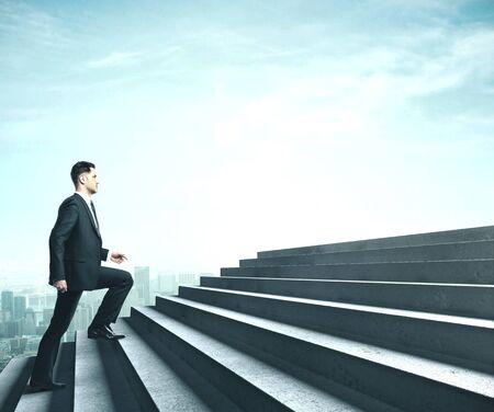 Hombre de negocios en traje caminando junto a la escalera en el cielo. Concepto de desafío empresarial Foto de archivo