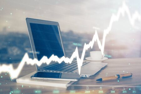 Stock market graph and table with computer background. Double exposure. Concept of financial analysis.