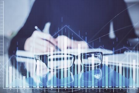 Forex chart hologram on hand taking notes background. Concept of analysis. Double exposure Stok Fotoğraf