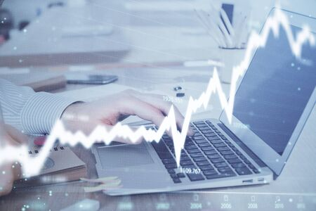 Multi exposure of stock market graph with man working on laptop on background. Concept of financial analysis.