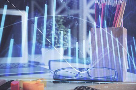 Ologramma grafico finanziario con gli occhiali sullo sfondo del tavolo. Concetto di affari. Esposizione doppia.