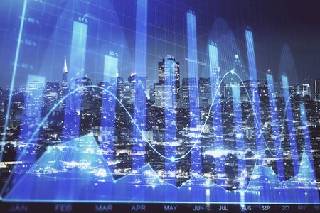 Financial graph on night city scape with tall buildings background double exposure. Analysis concept. 写真素材