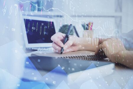 Financial graph displayed on womans hand taking notes background. Concept of research. Double exposure 写真素材