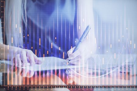 A woman hands writing information about stock market in notepad. Forex chart holograms in front. Concept of research. Reklamní fotografie