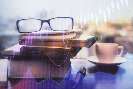 Financial graph hologram with glasses on the table background. Concept of business. Double exposure.