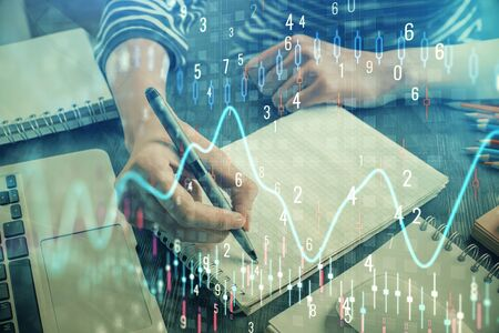 Financial chart drawn over hands taking notes background. Concept of research. Double exposure Reklamní fotografie