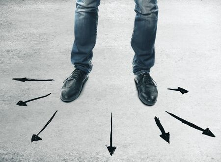 Foot and businessman stand on black arrows on abstract gray background. Different direction and path concept