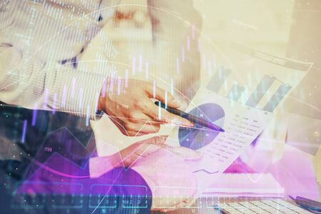 Financial trading graph double exposure with man desktop background.