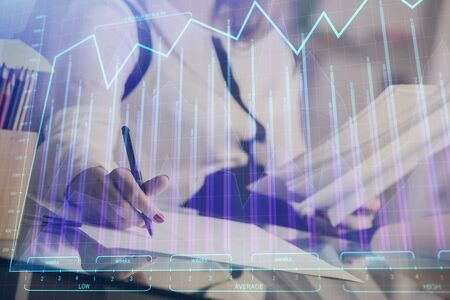 A woman hands writing information about stock market in notepad. Forex chart holograms in front. Concept of research. Zdjęcie Seryjne