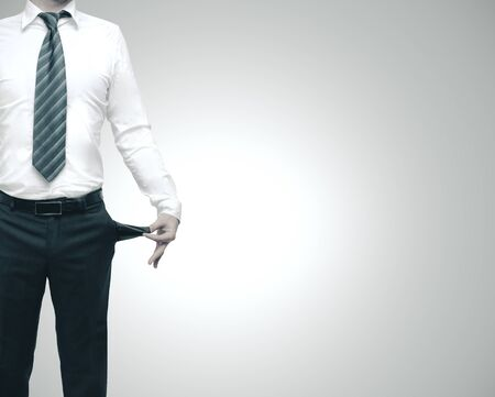 Businessman turning his empty pockets inside out. Isolated in gray. Business problems concept Foto de archivo