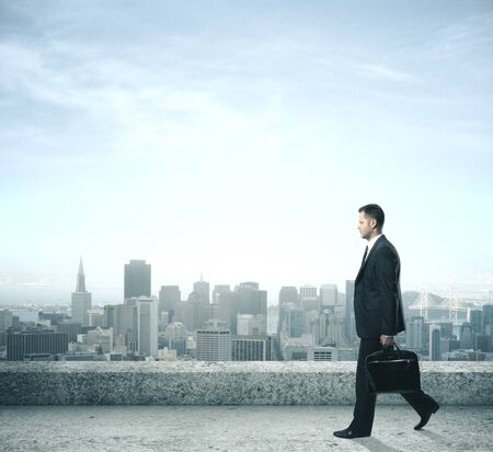 Businessman with briefcase walking on roof and looking to night city