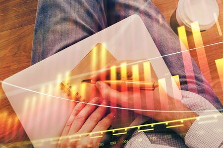 Double exposure of hands writing in notepad with stock market chart. Stok Fotoğraf