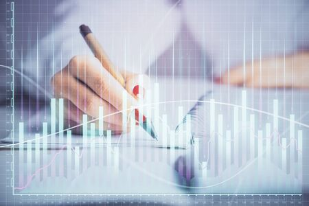 Double exposure of womans hands making notes with forex graph hologram. Concept stock market analysis.