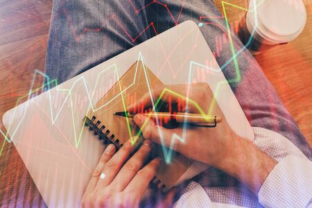 Double exposure of hands writing in notepad with stock market chart. Concept of research and analysis.