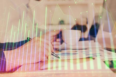 Double exposure of mans hands writing notes of stock market with forex graph. Side View. Concept of research and trading. Stok Fotoğraf