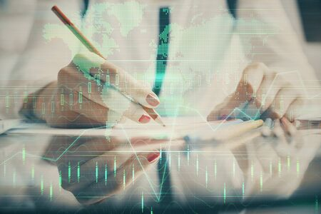 A woman hands writing information about stock market in notepad. Forex chart holograms in front. Concept of research. Stok Fotoğraf