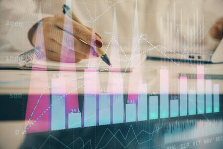 Double exposure of womans hands making notes with forex graph hologram. Concept technical analysis.