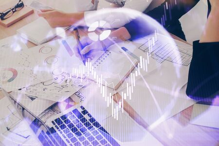 A woman hands writing information about stock market in notepad. Forex chart holograms in front. Concept of research. Double exposure Stok Fotoğraf