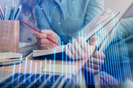 A woman hands writing information about stock market in notepad. Forex chart holograms in front. Concept of research. Multi exposure