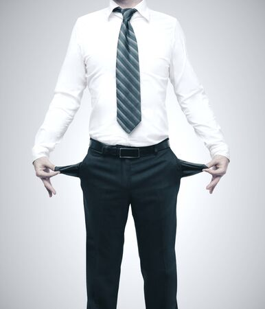 Businessman turning his empty pockets inside out. Isolated in gray. Business problems concept