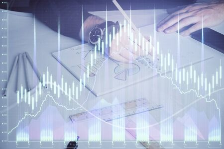 Double exposure of mans hands writing notes of stock market with forex chart.