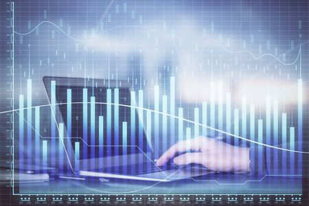 Double exposure of mans hands writing notes with laptop of stock market with forex graph background. Top View. Concept of research and trading. Banco de Imagens