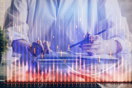 Financial forex graph drawn over hands taking notes background. Concept of research. Double exposure