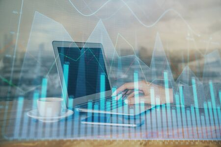 Double exposure of businessmans hands with laptop and stock market graph background. Concept of research and trading. Banco de Imagens
