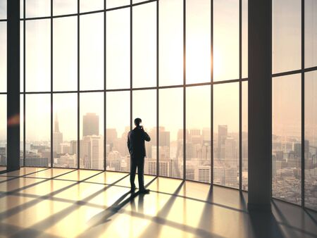 Businessman standing in contemporary office with big window and talking. Business and motivation concept.