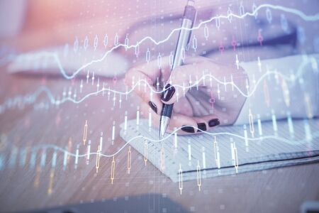 Multi exposure of hands making notes with forex chart huds. Stock market concept. Reklamní fotografie