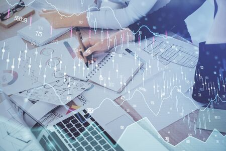 A woman hands writing information about stock market in notepad. Forex chart holograms in front. Concept of research. Double exposure Reklamní fotografie
