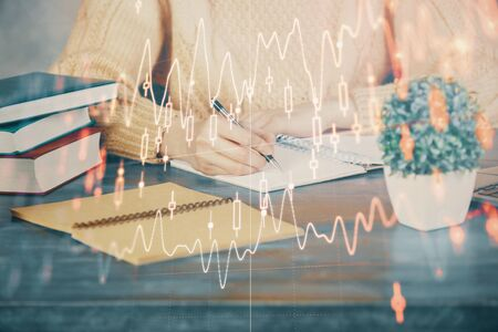 Forex graph on hand taking notes background. Concept of research. Double exposure