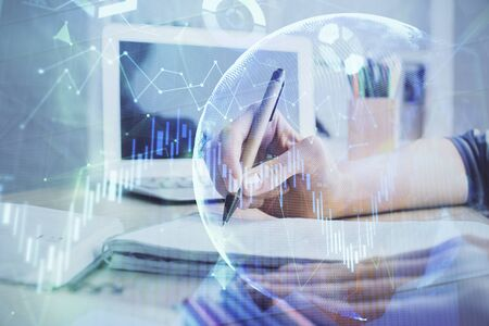 Financial forex charts displayed on womans hand taking notes background. Concept of research. Double exposure Reklamní fotografie
