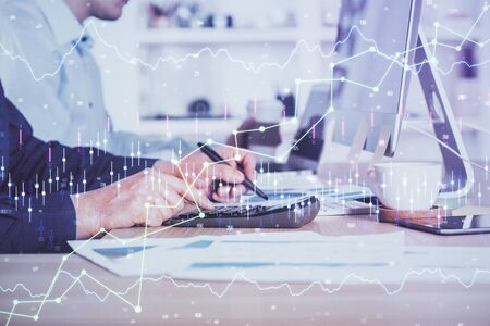 Forex graph with businessman working on computer in office on background. Concept of hardworking. Closeup. Multi exposure. Reklamní fotografie