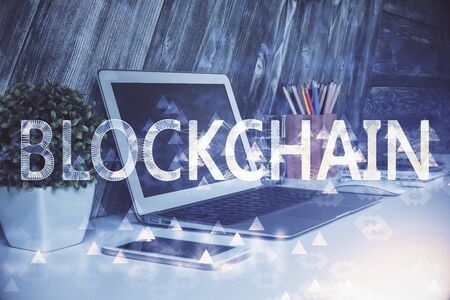 Multi exposure of blockchain theme hologram and table with computer background. Concept of bitcoin crypto currency. Reklamní fotografie