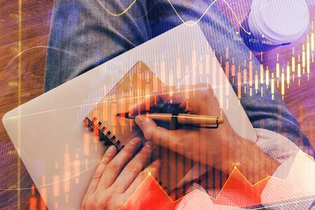 Double exposure of hands writing in notepad with stock market chart. Reklamní fotografie