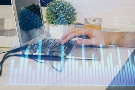 Multi exposure of graph with man typing on computer in office on background. Concept of hard work. Closeup. 版權商用圖片