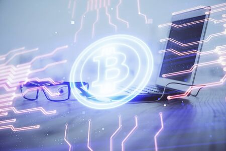 Multi exposure of blockchain theme hologram and table with computer background. Concept of bitcoin crypto currency. Фото со стока