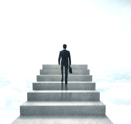Businessman with briefcase climbing to stairs on sky background. Success and startup concept.