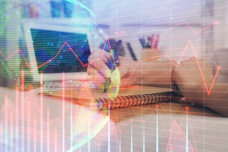 Financial graph displayed on womans hand taking notes background. Concept of research. Double exposure Stok Fotoğraf