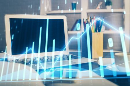Stock market graph on background with desk and personal computer. Double exposure. Concept of financial analysis.