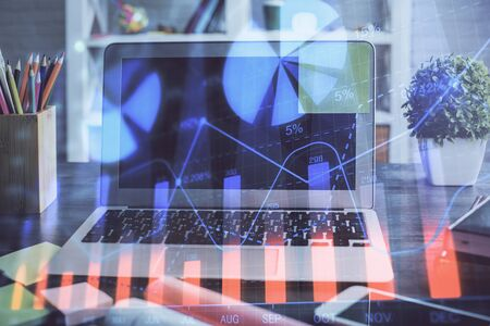 Forex market graph hologram and personal computer on background. Multi exposure. Concept of investment.