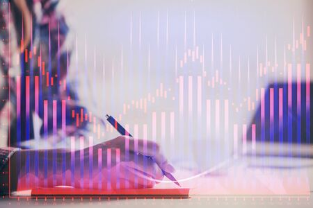 A woman hands writing information about stock market in notepad. Forex chart holograms in front. Concept of research. Double exposure Zdjęcie Seryjne