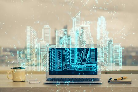 Desktop computer background in office and big town buildings hologram drawing. Double exposure. Smart city concept. Stock fotó