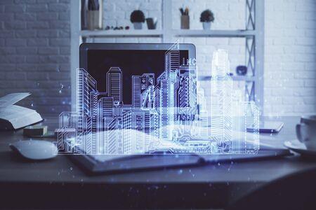 Desktop computer background in office and big town buildings hologram drawing. Double exposure. Smart city concept. Standard-Bild - 138461694