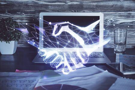 Desktop computer background in office and handshake hologram drawing. Double exposure. Pertnership concept. Reklamní fotografie
