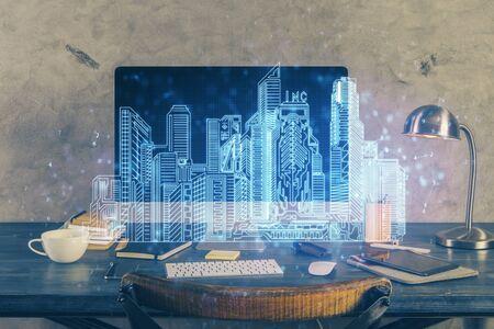 Desktop computer background in office and big town buildings hologram drawing. Double exposure. Smart city concept. Reklamní fotografie