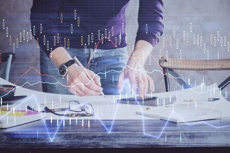 Multi exposure of man standing and planing investment with stock market forex chart background. Concept of research and trading. Reklamní fotografie